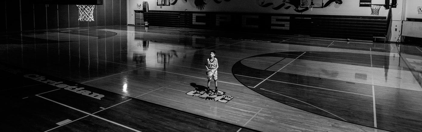 Image of a man playing basketball in a sports hall